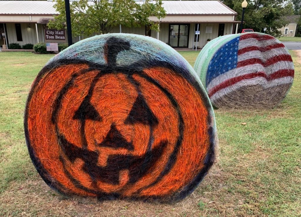 Fall-themed painted hay bale - pumpkin on hay bale with American flag hay bale in the background.