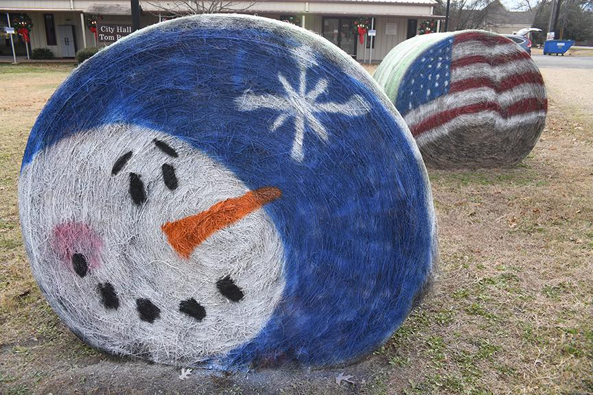 Hay bales painted with a snowman and a US Flag on City Hall Lawn