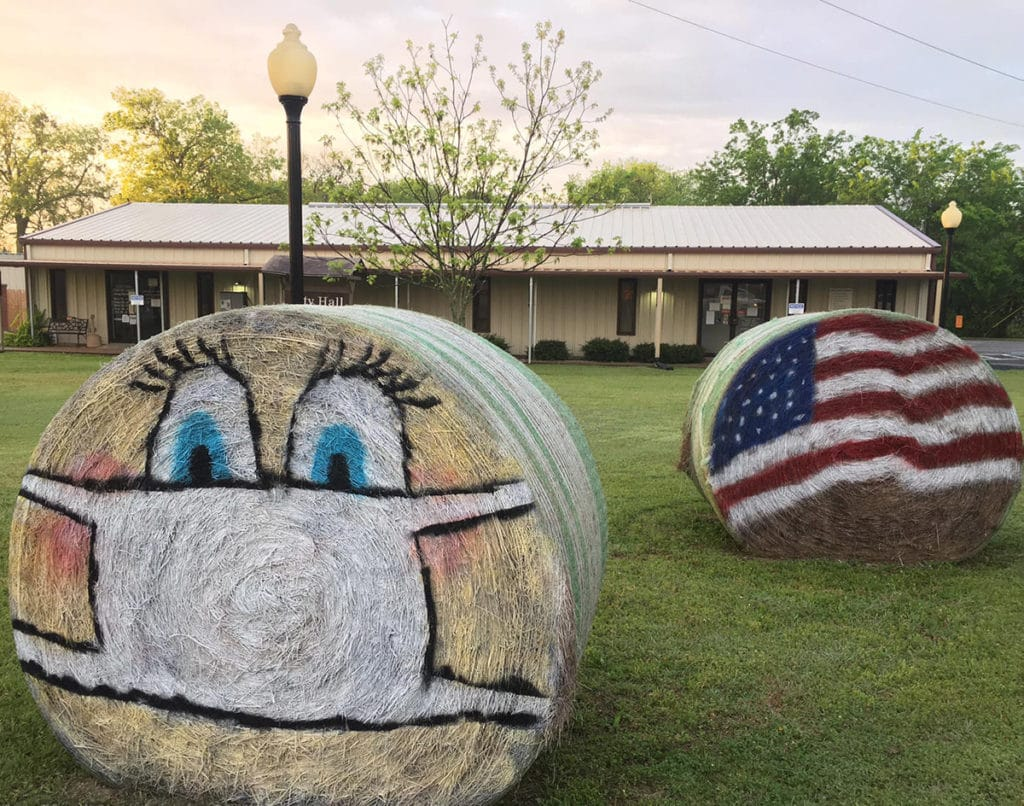 Hay Bale art with a character wearing a mask, recognizing our COVID-19 essential workers
